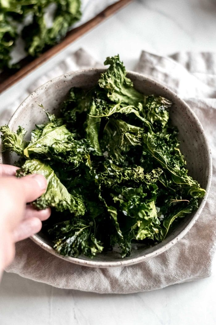 Hand reaching for some baked crispy kale chips.