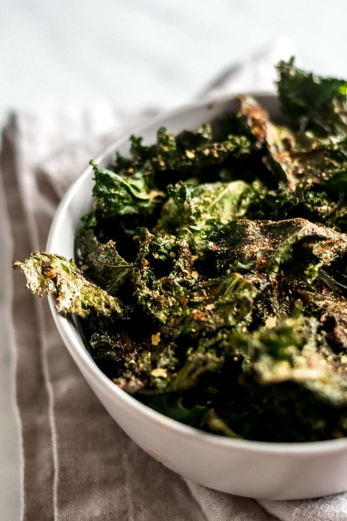 Close up of all-dressed kale chips in a white bowl.