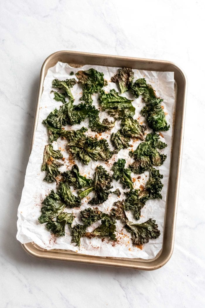Baking tray with baked homemade kale chips with spices.