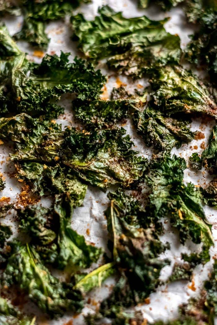 Spiced baked kale chips on a baking tray with parchment paper.