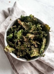 White bowl filled with spiced all-dressed kale chips.