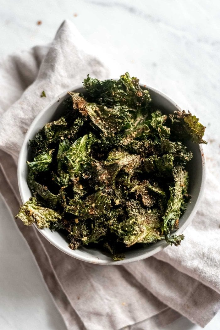 White bowl filled with all-dressed kale chips.