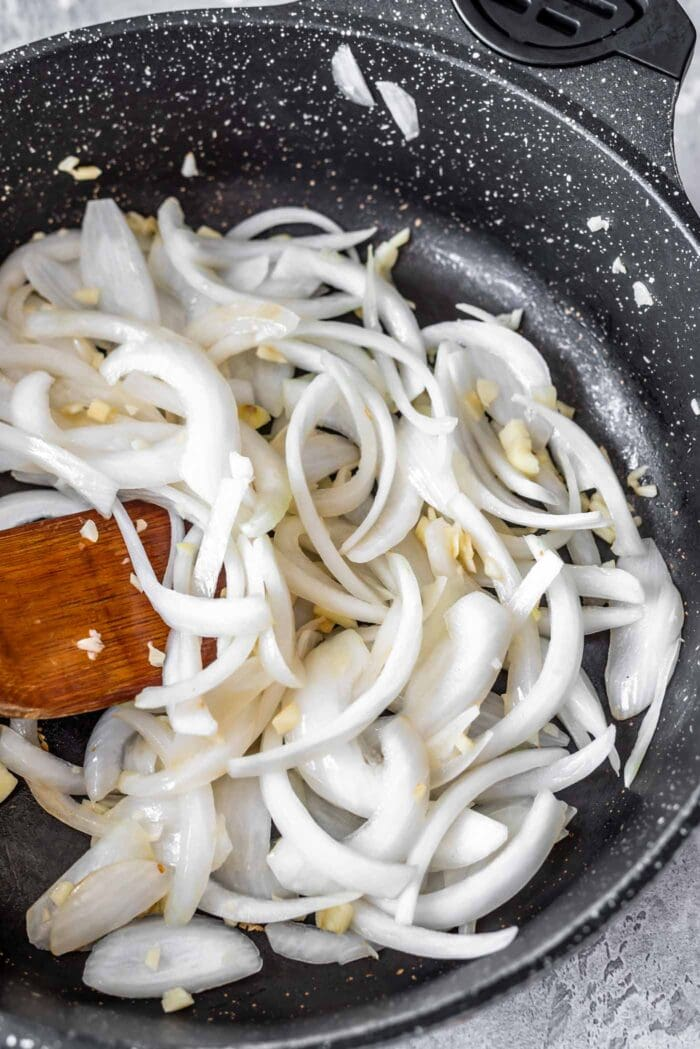 Sliced onions and garlic in a skillet with a wooden spoon.