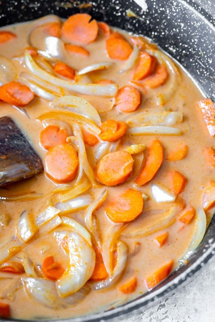 Sliced carrots and onion in a skillet with coconut milk and red curry paste.