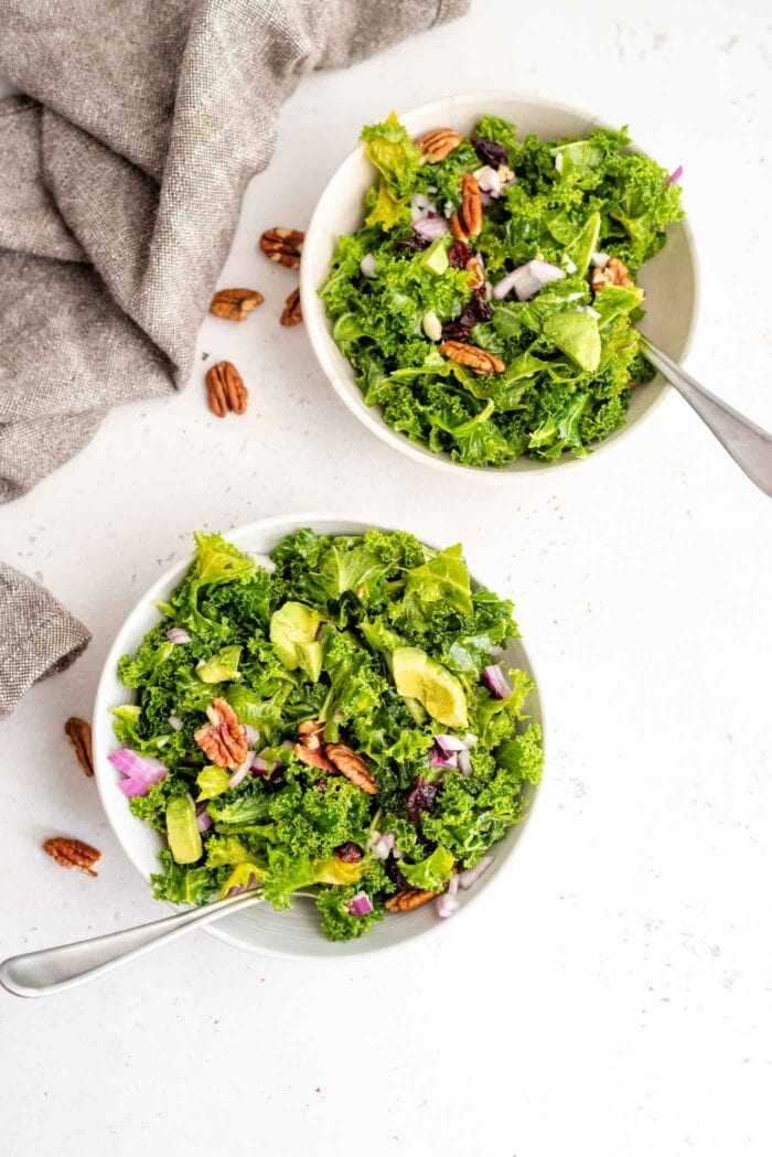 Two bowls of kale salad sitting on a white surface with some pecans scattered around.