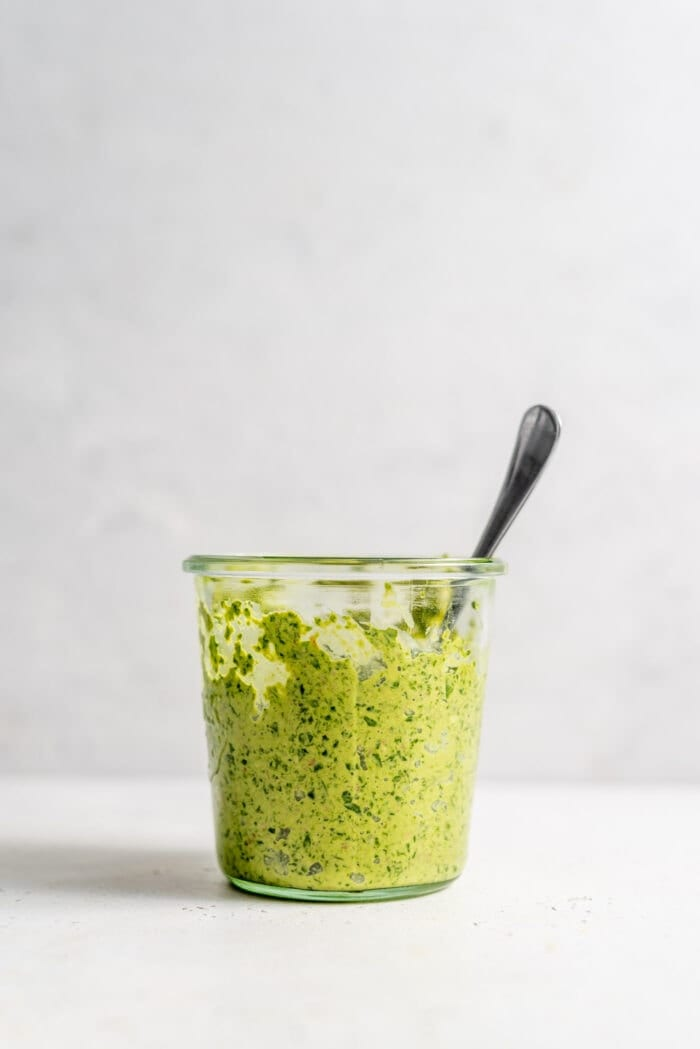 Jar of vegan spinach pesto with a spoon in it.