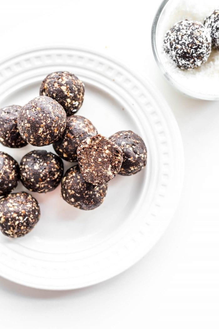 Chocolate raw vegan hazelnut truffles coated in coconut on a white plate.