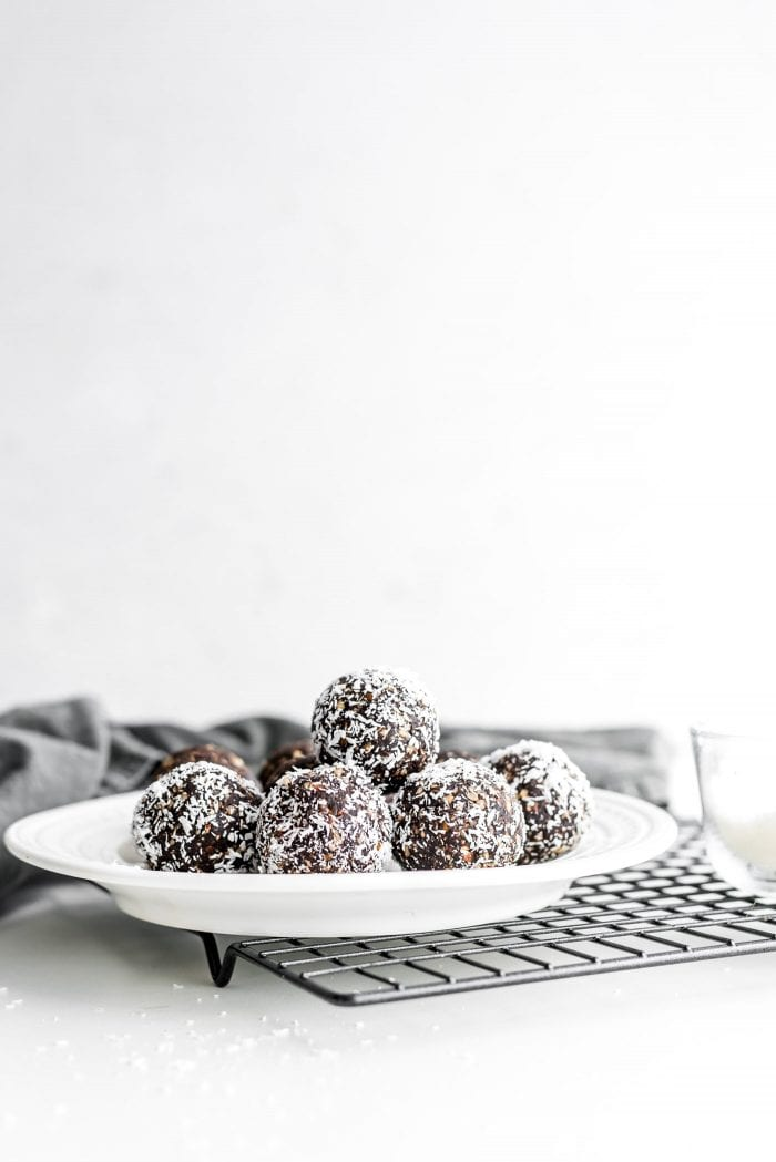 Pile of raw vegan hazelnut truffles on a white plate sitting on a cooling rack.
