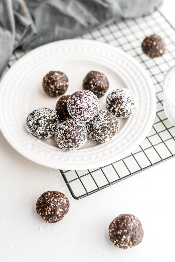 No-Bake Raw Vegan Hazelnut Truffles coated in coconut on a white plate.