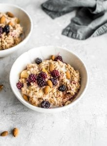 Oven baked steel cut oats in a small bowl with blackberries, maple syrup, almond milk and almonds.