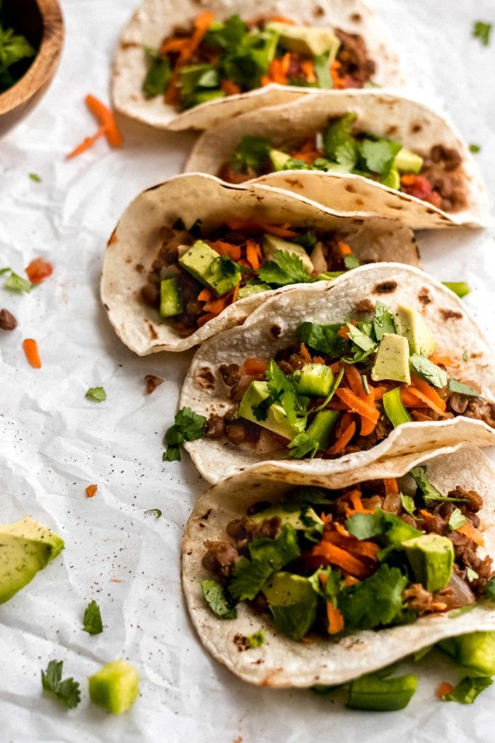 5 vegan lentil tacos with avocado, salsa, carrot and cilantro.