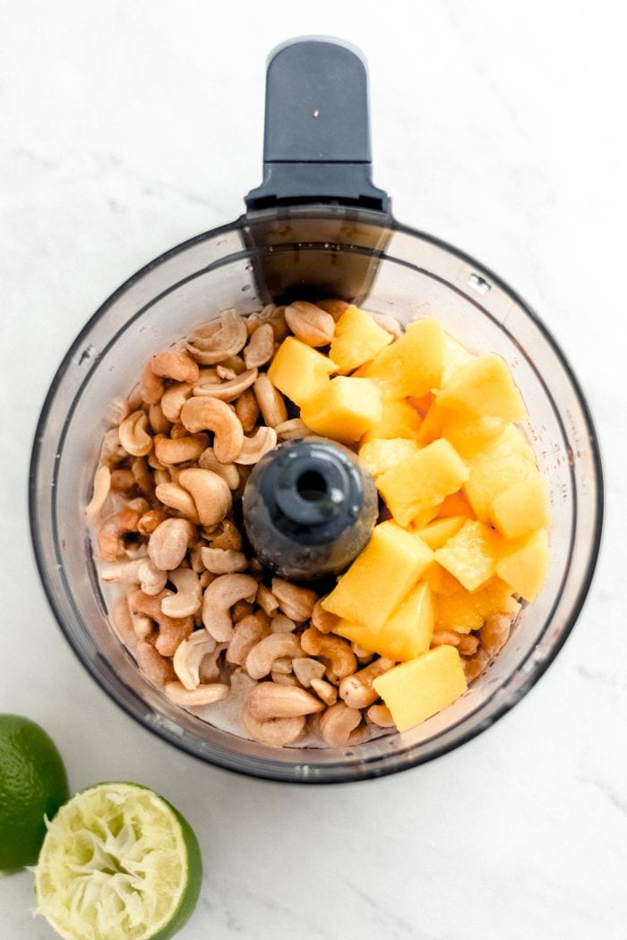 Raw cashews and mango in a food processor.