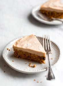Large slice of raw carrot cake on a white plate with a fork.