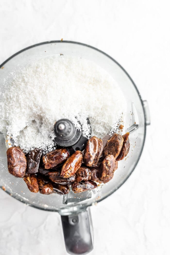 Dates, coconut oil and shredded coconut in a food processor.