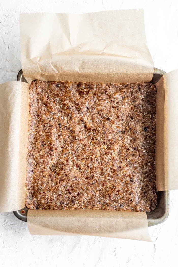 Raw coconut bars pressed into a baking pan lined with parchment paper.