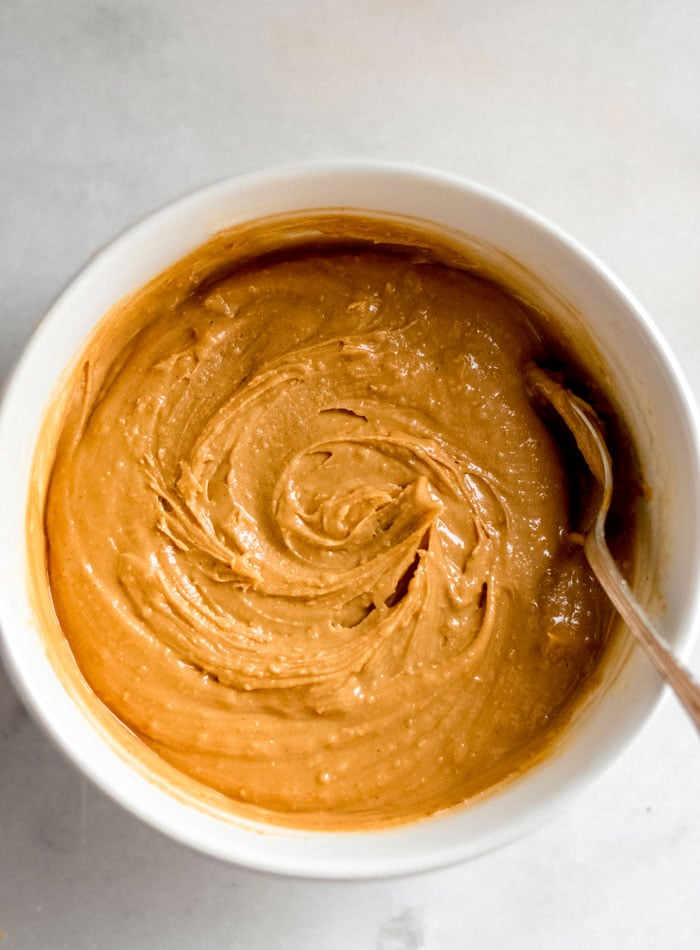 Peanut butter in a mixing bowl with a sppoon.