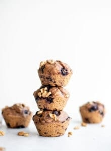 A stack of healthy vegan blueberry muffins sitting on a white surface.