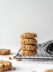 Stack of gluten-free vegan coconut almond date cookies sitting on a cooling rack.
