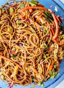 A peanut noodle salad with chopped vegetables in a large mixing bowl.