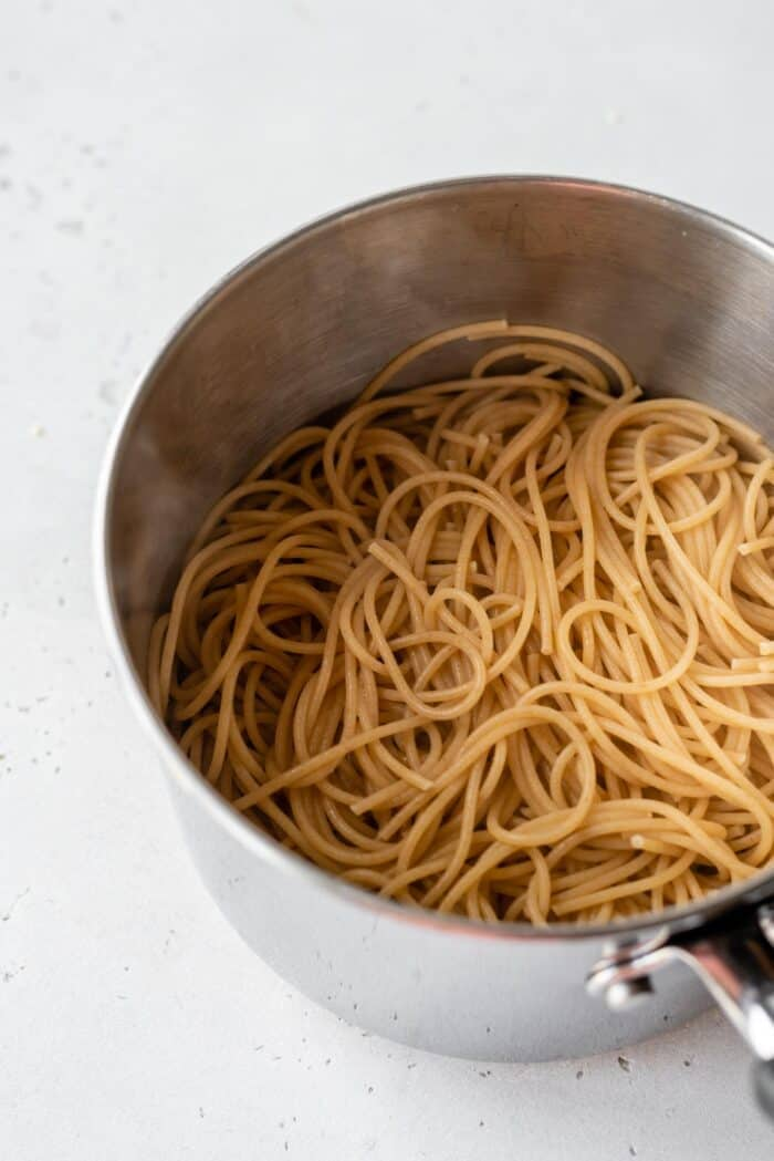 Cooked spaghetti noodles in a pot.