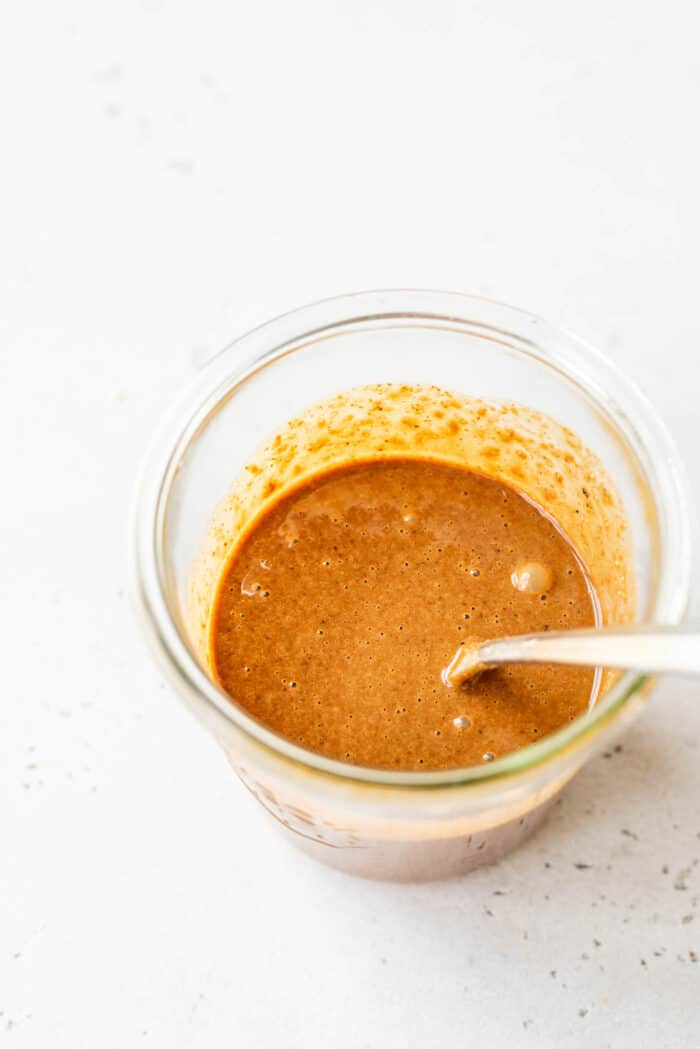 Creamy peanut sauce in a glass jar with a spoon.