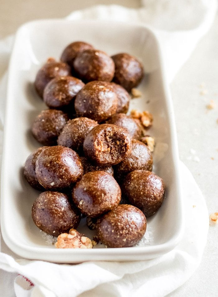 A plate of gingerbread balls, one on top has a bite out of it.