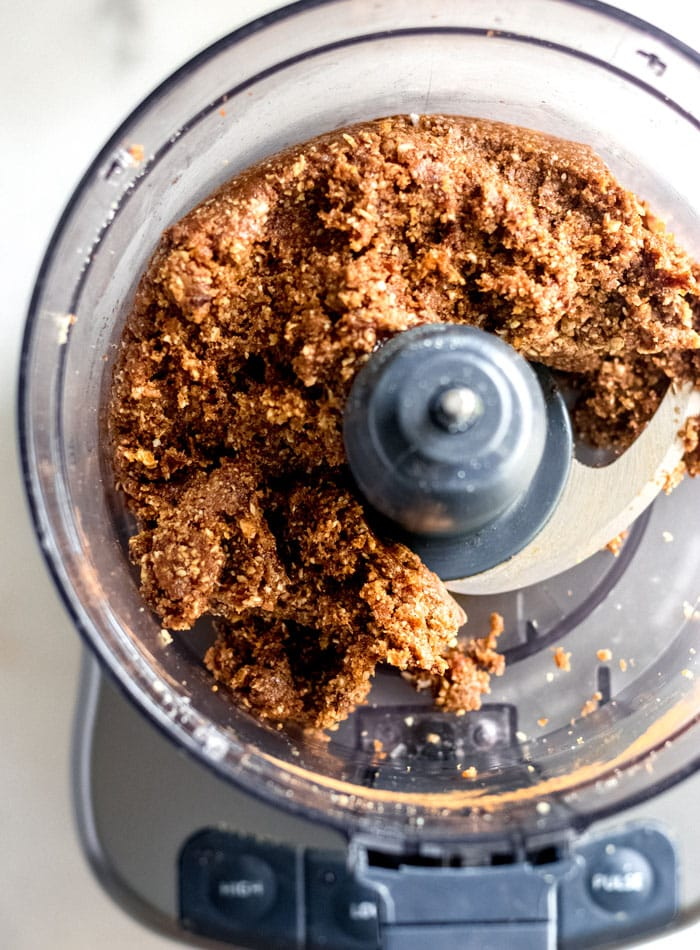 Overhead image of energy ball dough in a food processor container.