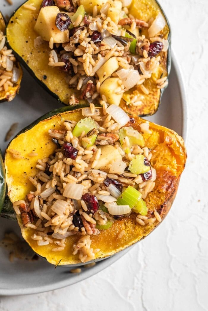 Two halves of roasted acorn squash stuffed with rice, cranberries, pecans, apple and celery.