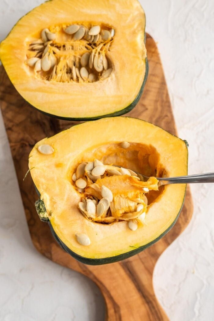 Two acorn squash halves with the spoon scooping out the seeds.