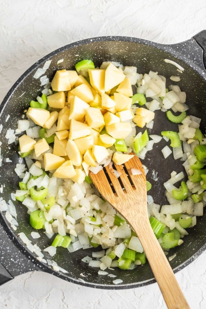 Apple, celery, onion and garlic in a skillet with herbs.
