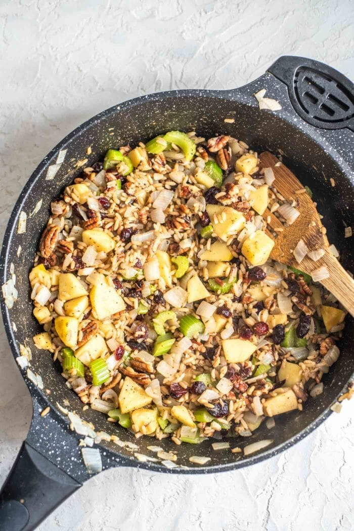 Rice, pecans, cranberries, apple and celery in a skillet.