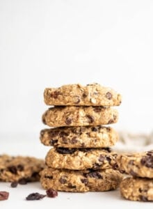 A stack of 5 vegan oatmeal raisins chocolate chips cookies against a white background with a few raisins scattered around.
