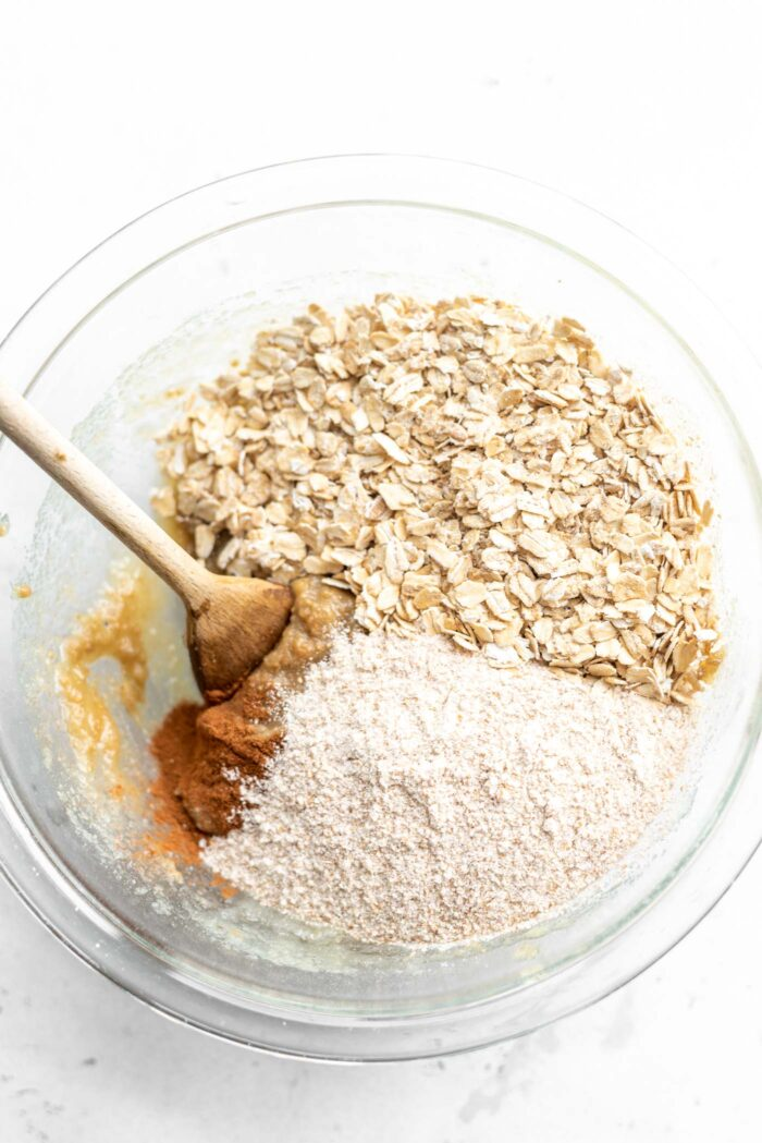 Whole wheat flour and rolled oats in a mixing bowl with a wooden spoon.