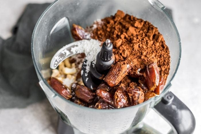 Dates, cacao powder, cashews and coconut in a food processor.