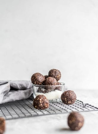 Vegan no-bake chocolate cashew coconut balls in a glass dish sitting on a cooling rack.