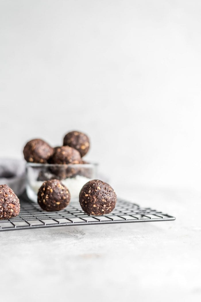 Vegan chocolate coconut ball on a baking cooling rack against a grey background.
