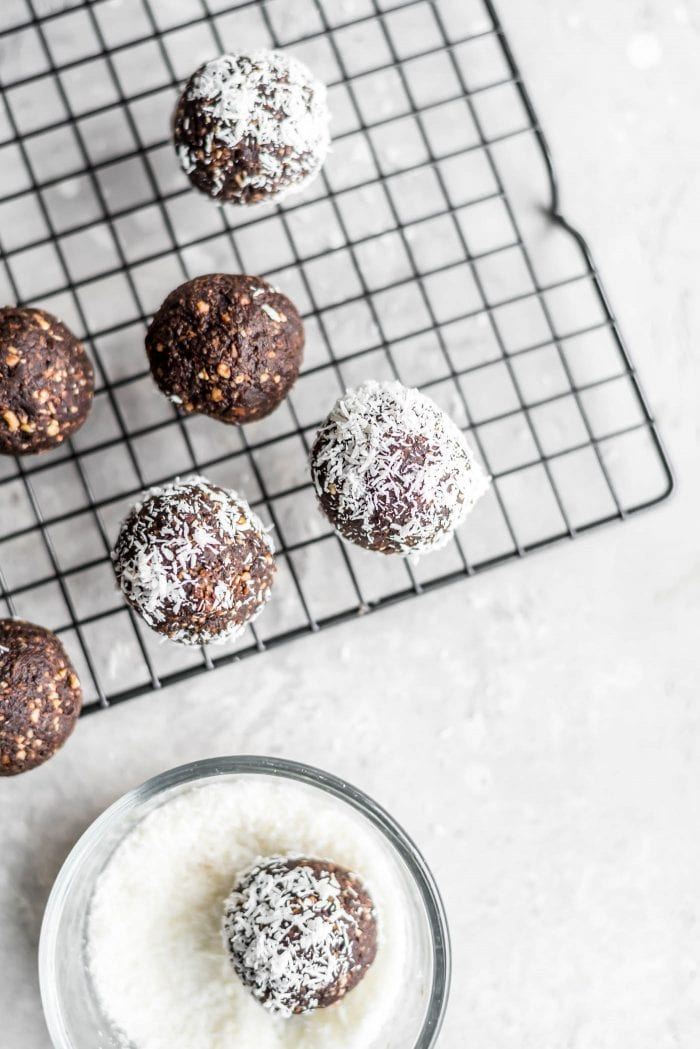 Overhead image of 7 no-bake vegan chocolate coconut balls rolled in coconut on a cooling rack.