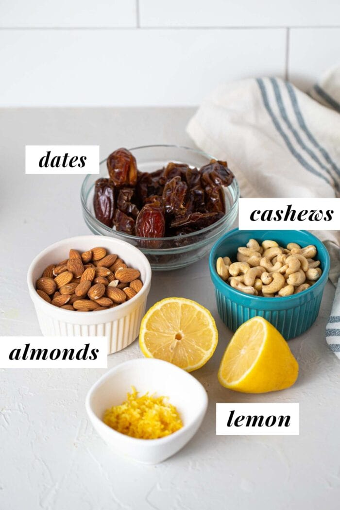 Dates, cashews, almonds and lemon zest in containers with labels.