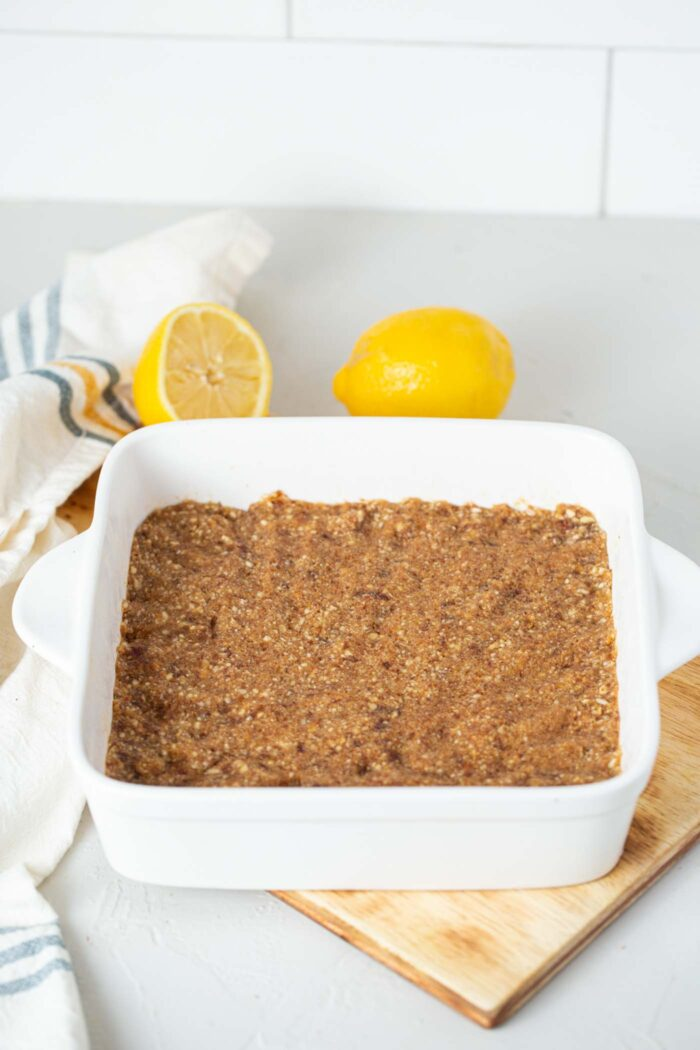 Raw energy bars pressed into a baking dish sitting on a counter.