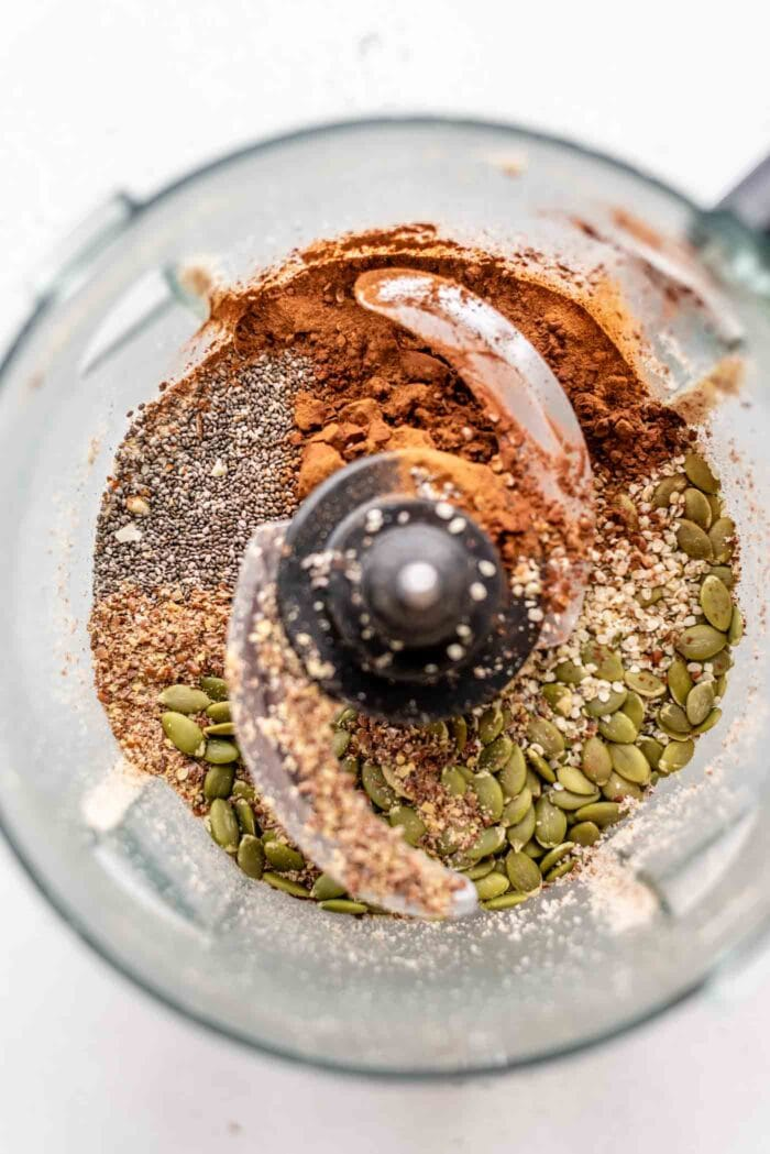 Chia seeds, pumpkin seeds, cocoa powder and hemp seeds in a food processor.