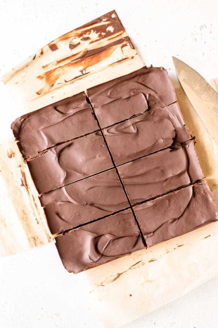 Sliced chocolate energy bars sitting on parchment paper.