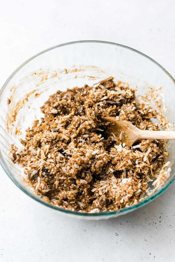 Raw dough for paleo coconut energy bars being mixed up in a glass mixing bowl.
