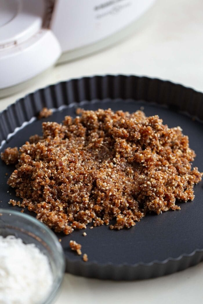 Crumbly no-bake raw pie crust in a small pie dish.