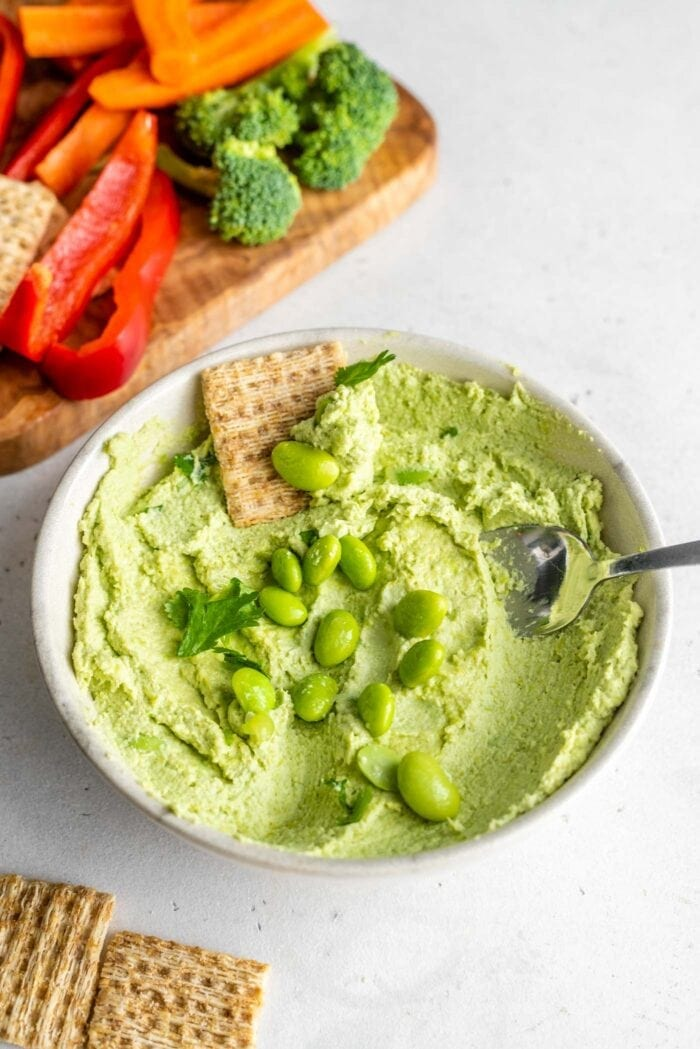 A spoon and cracker scooping edamame hummus out of a small bowl sitting on a white surface.