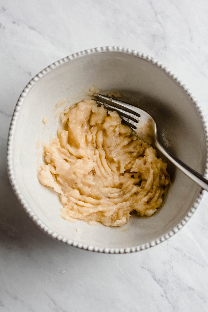 Bowl of mashed banana with a fork.