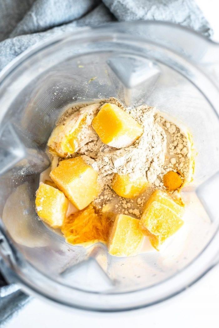Frozen mango, orange, almond milk, protein powder, frozen banana and turmeric in a blender.
