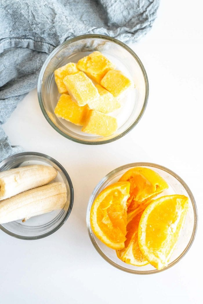Orange slices, frozen mango and frozen banana in glass dishes.