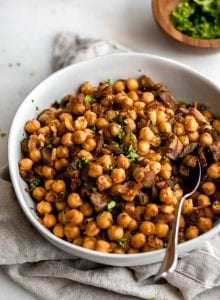 Easy vegan spiced chickpeas with mushroom and garlic in a white bowl with a spoon.