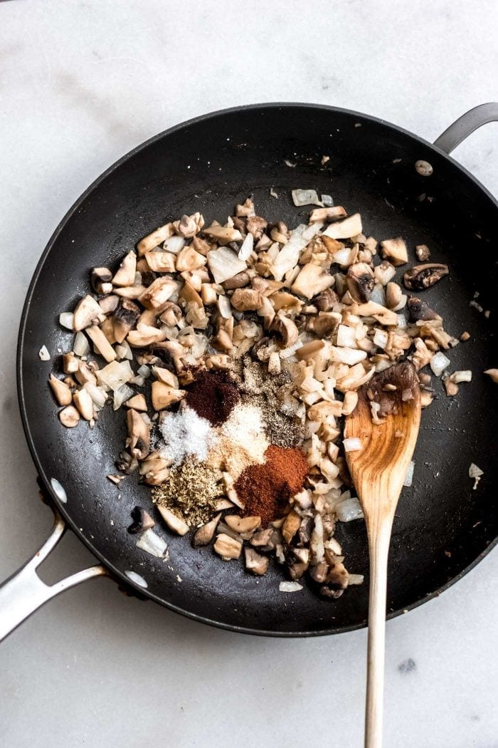 Mushrooms, onions and spices in a skillet with a wooden spoon for making spiced chickpeas.