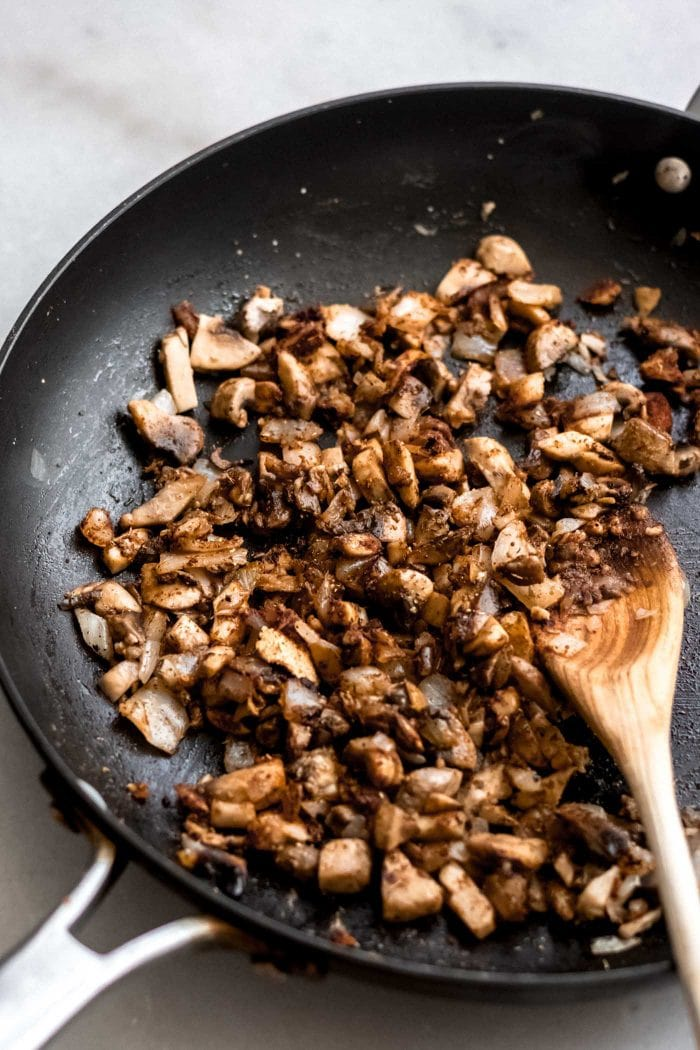 Sautéed mushrooms and onions in a skillet.